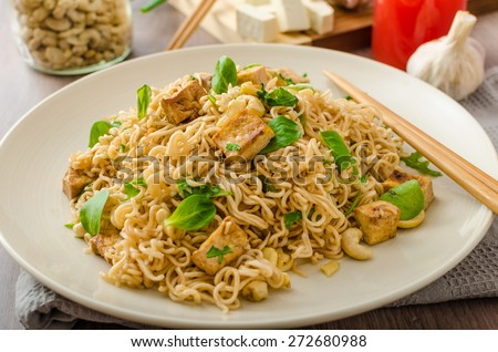 Chinese noodles with tofu and cashew nuts, with garlic, fresh salad on top - stock photo