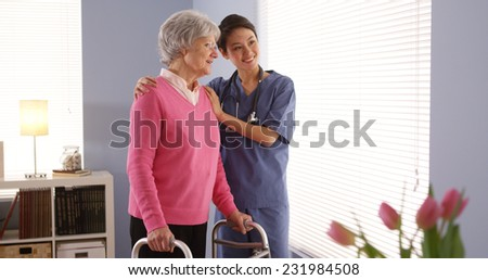 Chinese nurse and elderly woman patient looking out window - stock photo