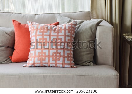 Chinese pattern  in orange and deep orange and gray pillows on light gray sofa set - stock photo