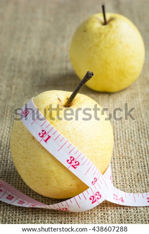 Chinese pear (Pyrus pyrifloraL) and measuring tape on hemp sack background. Concept Healthy fruit, weight lose, diet. - stock photo