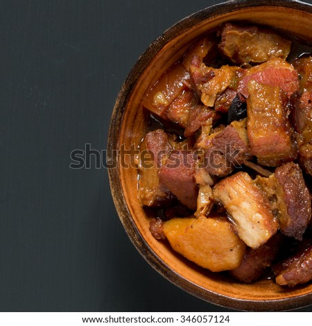 Chinese pork belly caramelized and braised in soy sauce with star anise, cinnamon and chilies. on black background - stock photo