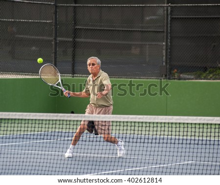 Chinese senior concentrating on the forehand volley. - stock photo