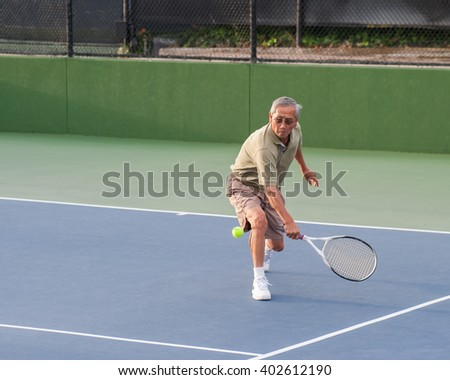 Chinese senior man coming in for low volley.  - stock photo