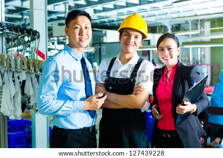 Chinese Shift supervisor or foreman, together with the owner or CEO and the Manager, standing proud in a factory - stock photo