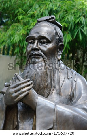 Chinese statue of Confucius with bamboo background - stock photo
