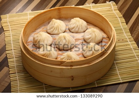Chinese steamed bun filled with pork and vegetables in bamboo steamer - stock photo