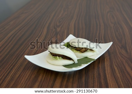 Chinese steamed bun sandwich of barbecue marinated pork. - stock photo