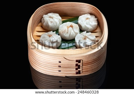 Chinese steamed dim sum in bamboo basket isolated on black  - stock photo