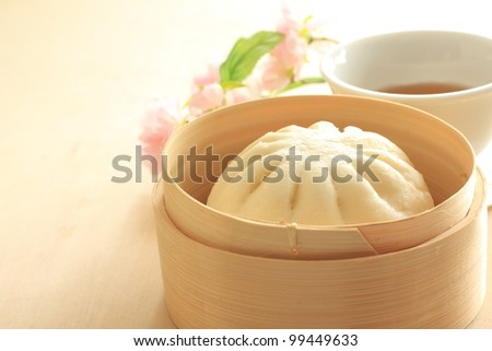 Chinese steamed dumpling, meat bun on bamboo steamer with hot tea