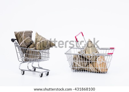Chinese sticky rice dumplings (Zongzi) made of sticky rice, reed/bamboo leaf in a wire shopping trolley and basket, ussually taken during Traditional Food festival to celebrate Dragon  - stock photo