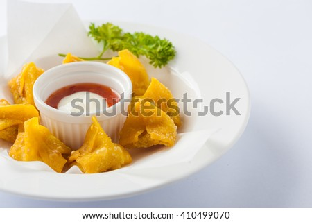 Chinese style deep-fried wonton with sweet and sour sauce in ceramic dish. - stock photo