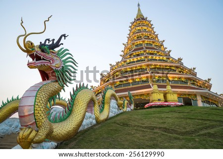 Chinese style nine level pagoda with dragon stairs in Thai temple under twilight sky - stock photo