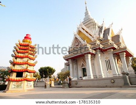 chinese style stepping stupa with colorful decorative ornaments isolated with blue sky background standing together with Shrine of the City Pillar Kohnkaen Khon Kaen province in north east Thailand - stock photo