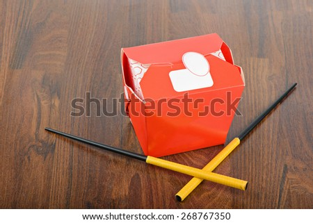 Chinese take away red food box with chopsticks on wooden background - stock photo
