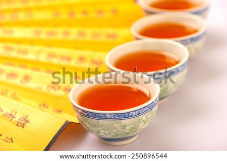 Chinese tea ceremony. Composition of crockery teacups surrounded by a Chinese hand fan isolated on white background with selective focus - stock photo
