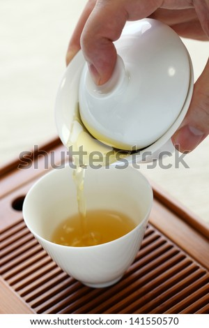 chinese tea serving, pouring from gaiwan in tasting cup