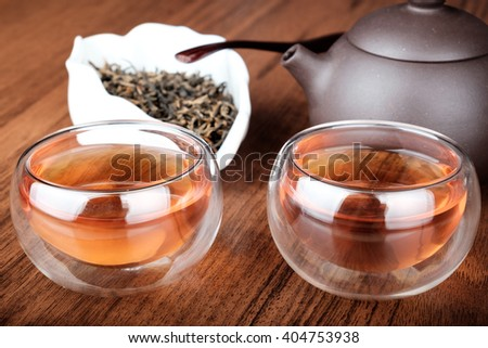 Chinese tea set with glass cups, porcelain brown teapot on wooden desk - stock photo