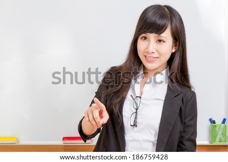 Chinese teacher in front of whiteboard with white shirt and black jersey - stock photo