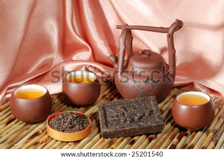 Chinese teapot and cups with black pu-erh tea from yunnan province in China. Leaves undergoes double fermentation and compressed into bricks. Healthy drink. - stock photo