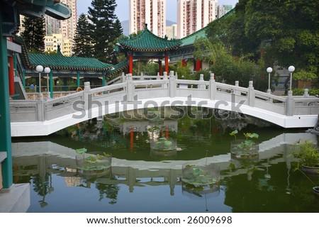 Chinese Water Garden Bridge and Reflection Amid Modern High Rise Buildings Wong Tai Sin Taoist Temple Kowloon Hong Kong - stock photo