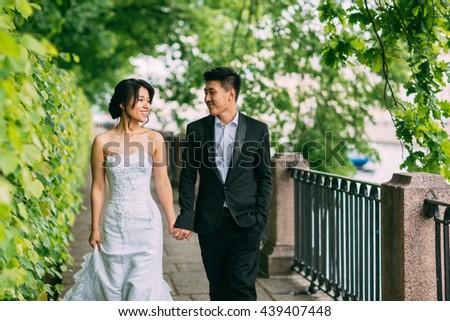 Chinese Wedding couple standing in the alley of green leaves - stock photo