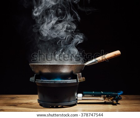 chinese wok pan on fire gas burner - stock photo