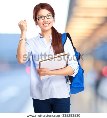chinese woman celebrating gesture with notebook - stock photo