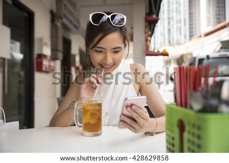 Chinese woman drinking an ice lemon tea, while sitting with her phone in an Asian food court or Hawker centre cafe. - stock photo