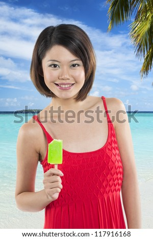 Chinese woman eating a lime green ice lolly on holiday. - stock photo