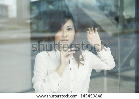 Chinese woman looking through a window - stock photo