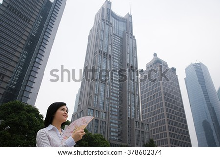 Chinese woman near skyscrapers - stock photo