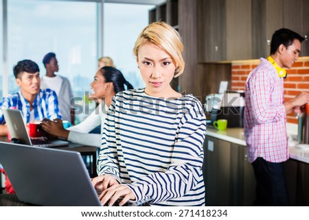 Chinese woman programmer in lounge of IT start-up with laptop, co-workers in the background - stock photo