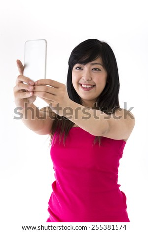 Chinese Woman taking 'selfie' self portrait photograph. Isolated on white background. - stock photo