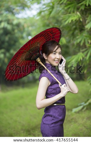 Chinese Woman talking on a Smart Phone and wearing a Cheongsam Chinese Dress with traditional umbrella.