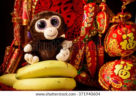 Chinese year of the monkey. Monkey sitting on bananas with Chinese new year red decorations.