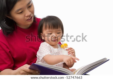 Chinese young woman story telling her cute daughter - stock photo