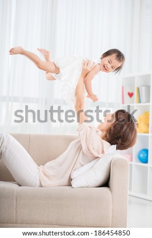 Chinese young woman throwing up her daughter playing at home - stock photo