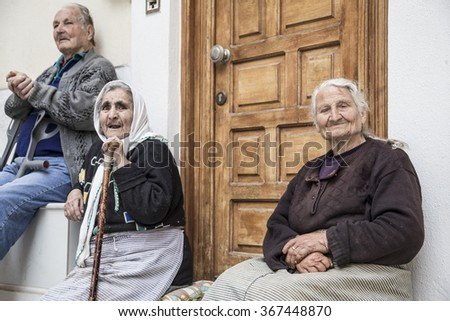 CHIOS ISLAND, GREECE - APRIL 24, 2015; Senior people sitting in front of their house in the Pirgi town of Chios Island in Greece. - stock photo
