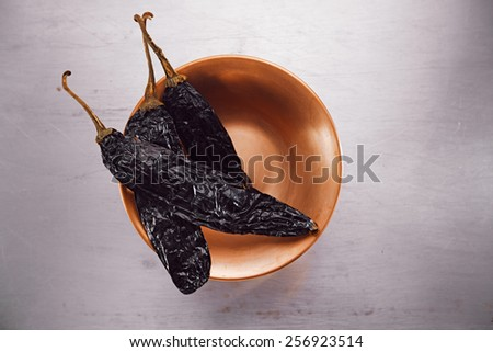 chipotle - jalapeno smoked whole chili  in copper bowl on  textured tin metal backdrop - stock photo