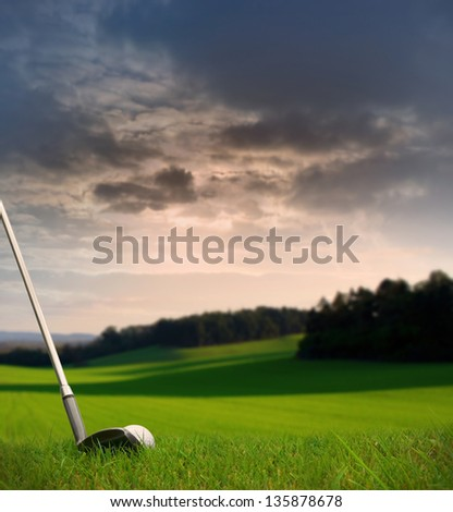 chipping a golf ball onto the green / fairway with golf club at sunset with copy space - stock photo