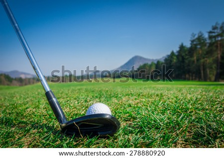 Chipping a golf ball onto the green with driver golf club. Green grass with forrest and mountains in the background. Soft focus or shallow depth of field. Back view - stock photo