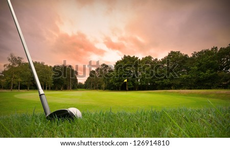 chipping a golf ball onto the green with golf club at sunset with copy space - stock photo