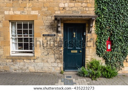 Chipping Campden, UK - August 12, 2015:  Limestone cottage entrance with green painted door,  white painted window, red mailbox amd green climbing plants