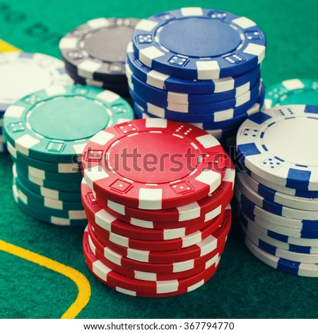 chips for poker on green playing table - stock photo