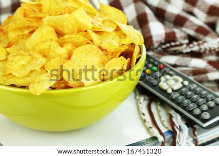 Chips in bowl, magazines, plaid and TV remote close-up - stock photo