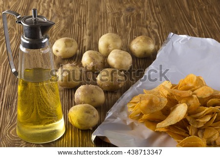 Chips, raw potato and jug of an oil.