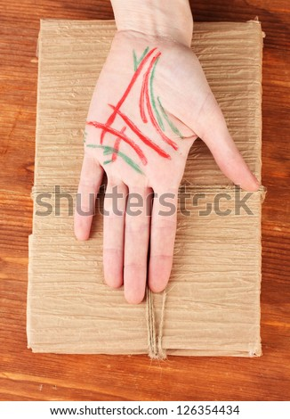 Chiromancy.Color contours on palm, on wooden background - stock photo