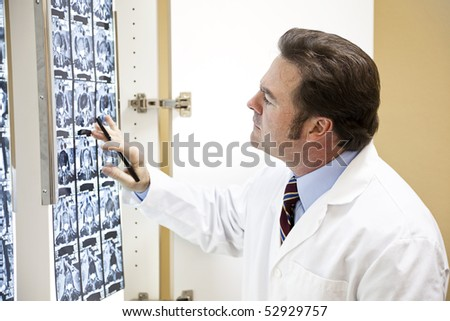 Chiropractic doctor examining the results of a CAT scan of the spine. - stock photo