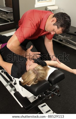 Chiropractor adjusting a female patient - stock photo