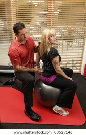 Chiropractor adjusting a patiant sitting on a ball - stock photo